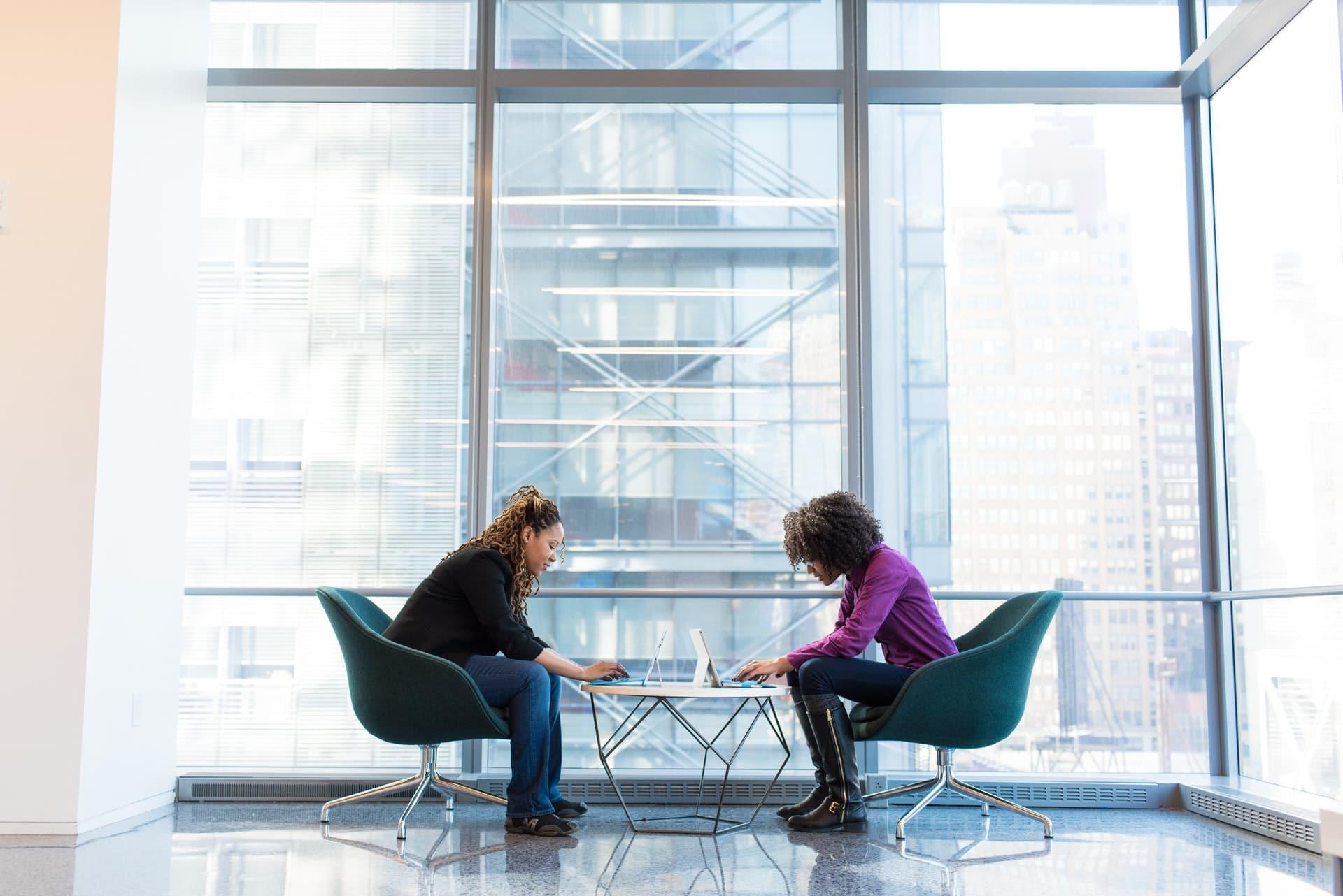 Deux personnes assises face à face, travaillant sur leur ordinateur